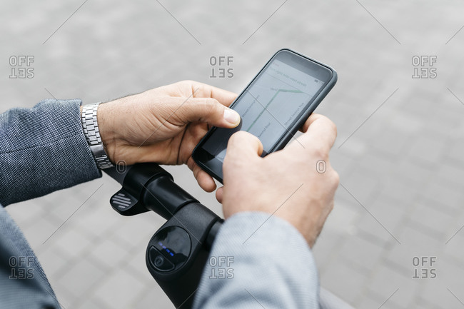 Close-up of businessman with electric scooter using cell phone