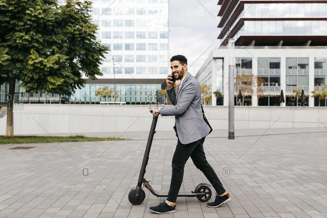 Casual young businessman with electric scooter talking on the phone in the city