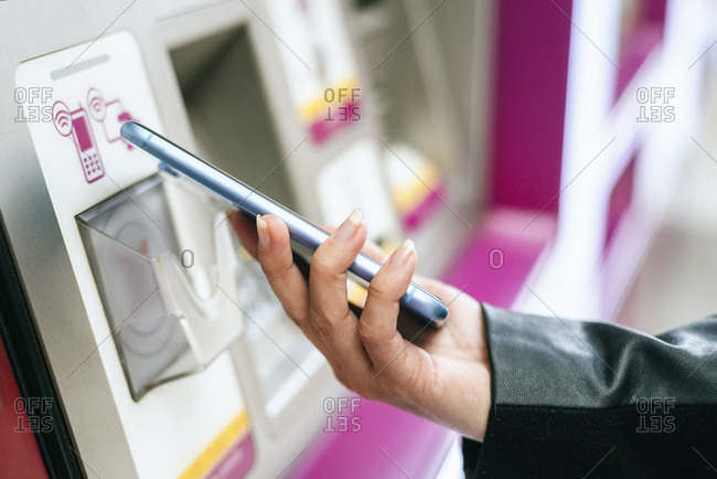 Close-up of woman paying with her smartphone