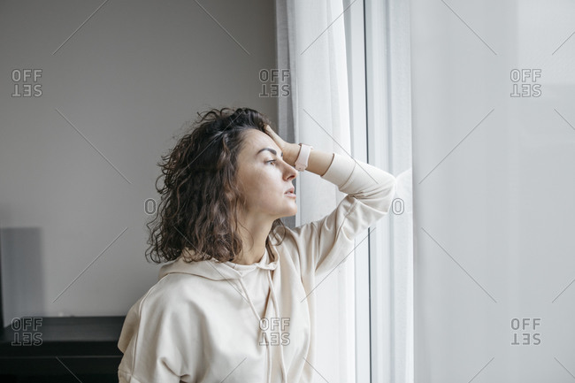 Portrait of pensive woman looking out of window