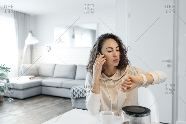 Portrait of woman looking at her smartwatch at home
