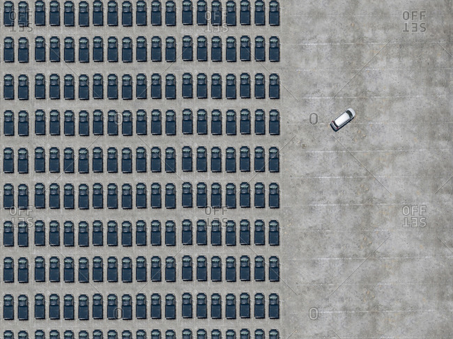 Aerial view of white car leaving parking lot filled with black cars