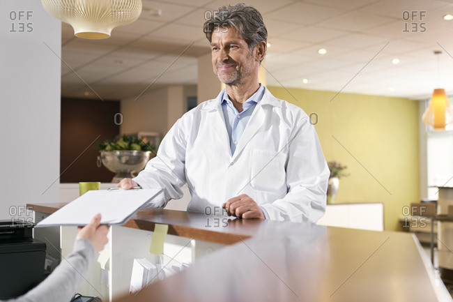 Doctor taking medical record at reception in his medical practice