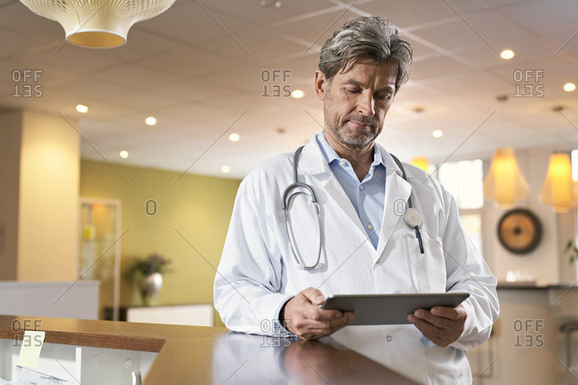 Doctor using tablet at reception in his medical practice
