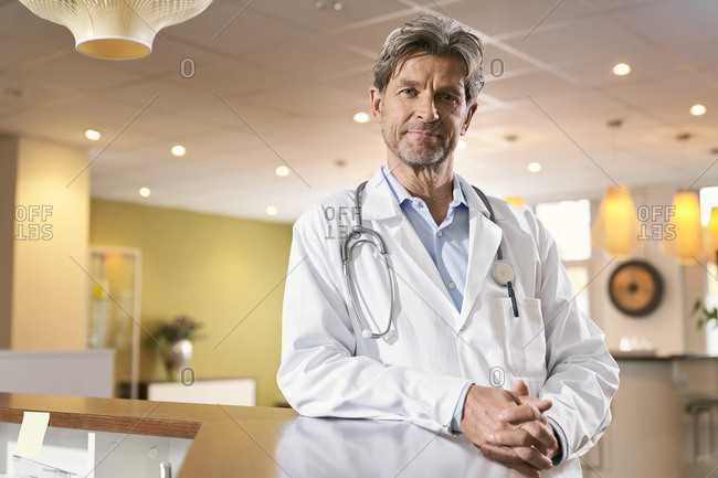 Portrait of confident doctor at reception in his medical practice
