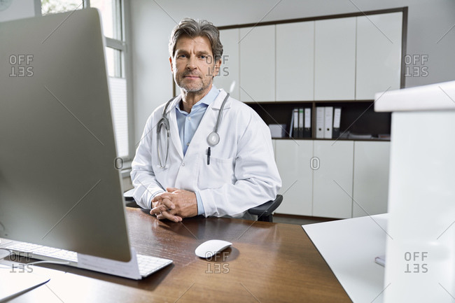 Portrait of confident doctor at desk in his medical practice