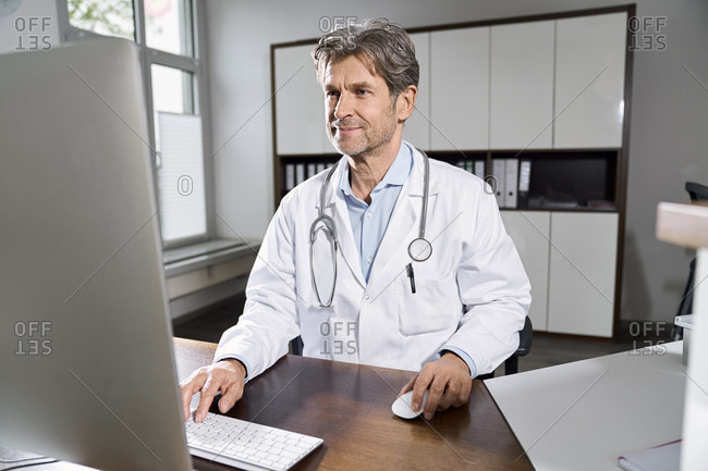 Doctor using computer at desk in his medical practice
