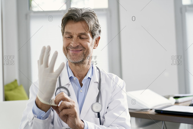Doctor putting on protective gloves in his medical practice