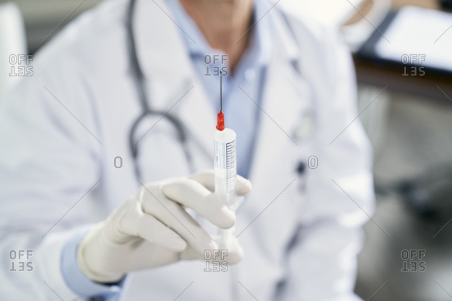 Doctor holding syringe in his medical practice