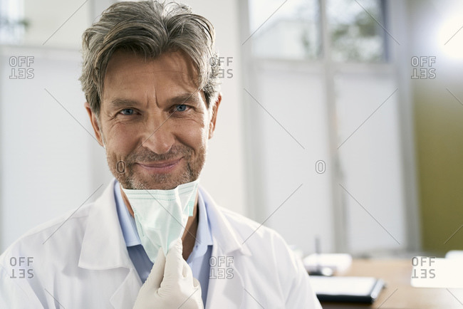 Portrait of smiling doctor with mask in his medical practice