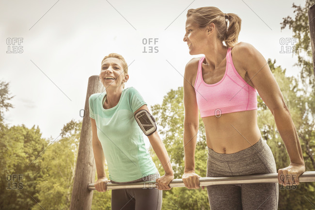 Women during workout on high bar in park