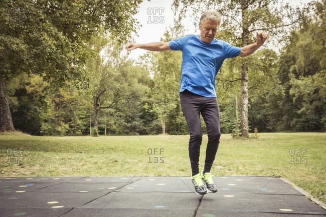 Senior man on trampoline mats