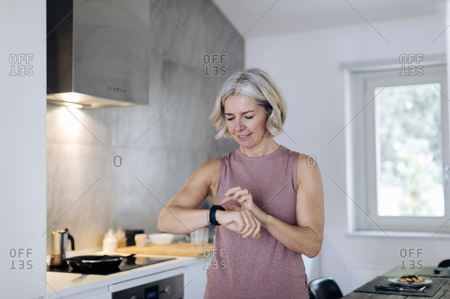 Mature woman using smartwatch in kitchen at home