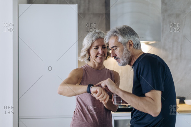 Mature couple using smartwatch in kitchen at home