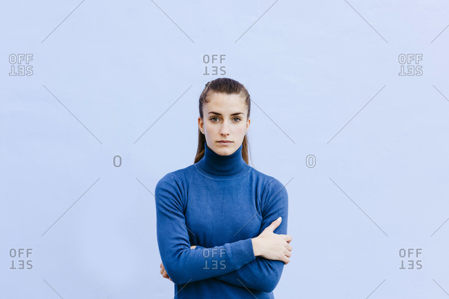 Portrait of young woman wearing blue turtleneck pullover in front of light blue wall
