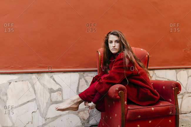 Portrait of barefoot young woman wearing red jacket sitting on lounge chair