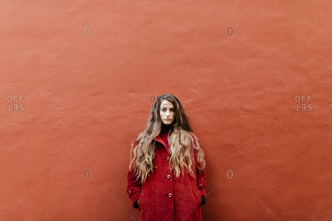 Portrait of self-confident young woman with long brown hair wearing red jacket leaning against red wall