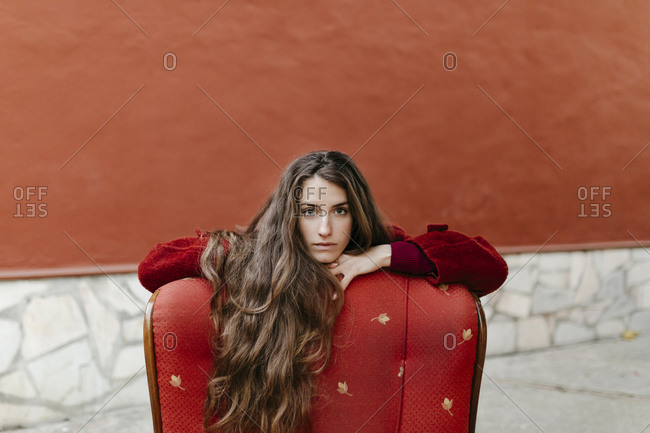 Portrait of self-confident young woman with long brown hair leaning on back rest of red lounge chair