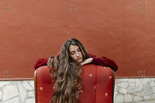 Portrait of young woman with long brown hair leaning on back rest of red lounge chair