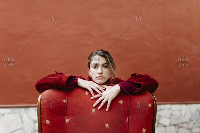 Portrait of serious young woman earning on back rest of red lounge chair