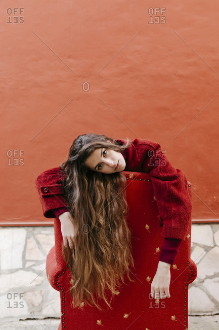 Portrait of young woman with long brown hair leaning on backrest of red lounge chair