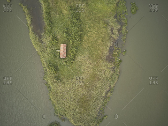 Benin- Grand Popo- Aerial view of secluded house on shore of green island