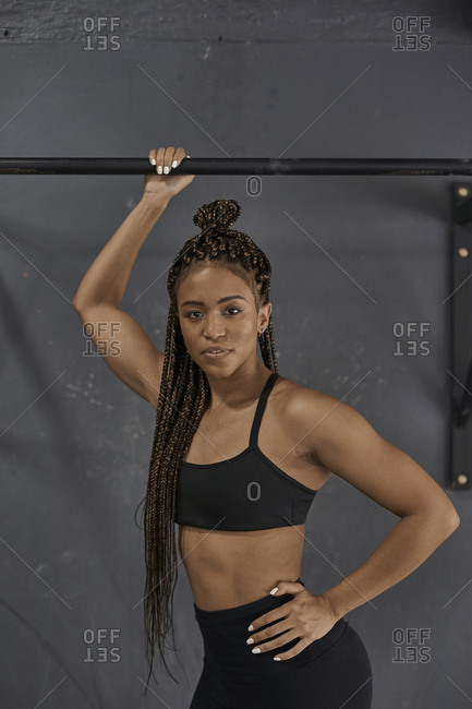 Female athlete standing at chin up bar- looking at camera