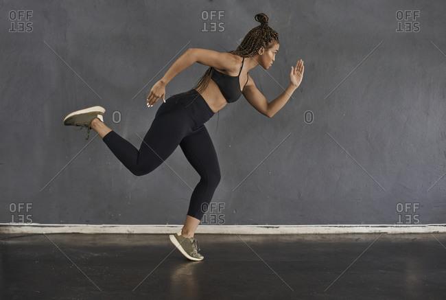 Female athlete doing running exercises in gym