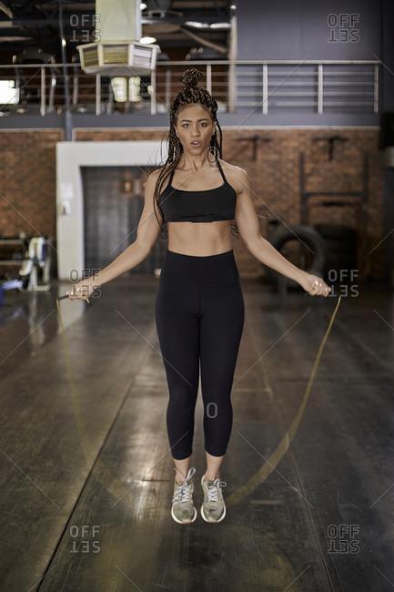 Female athlete skipping rope in gym