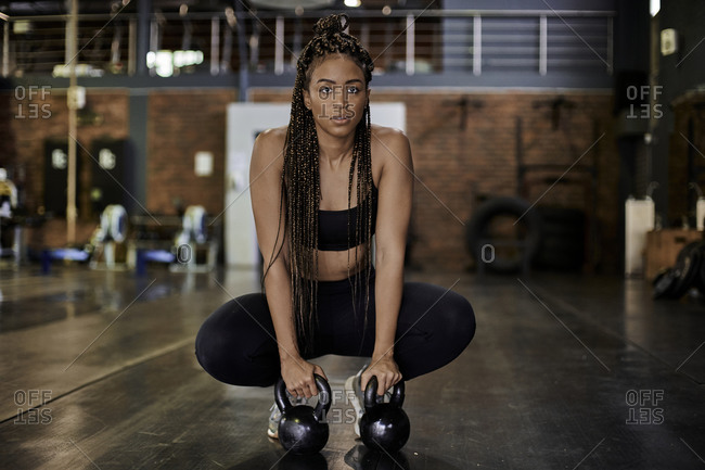 Female athlete training with kettlebells in gym