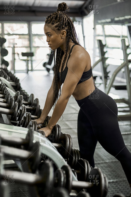 Female athlete choosing weights for training in gym
