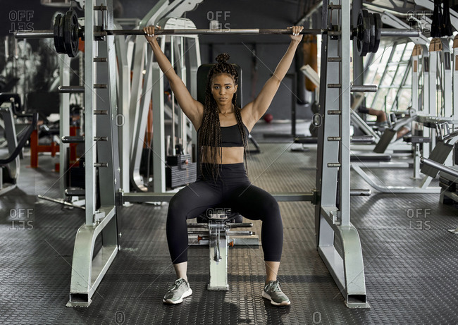 Female athlete weight lifting in gym