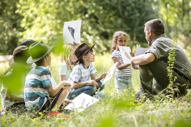 School children doing nature studies- holding pictures of animals