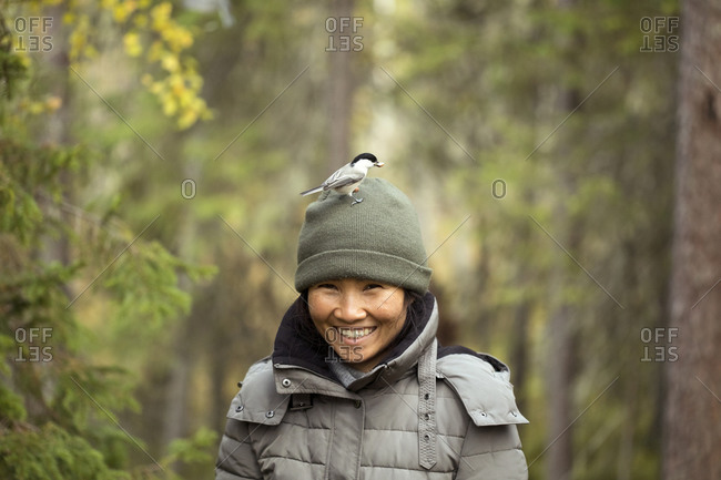 Portrait of woman with willow tit- Poecile montanus- on her hat