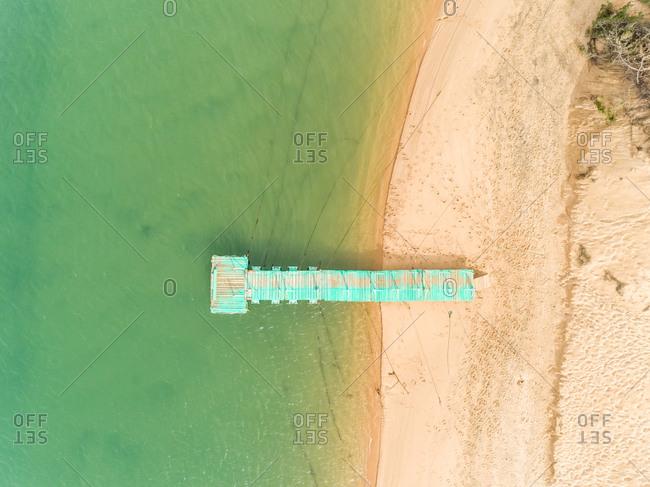 Aerial view of Praia das Furnas with a pier over turquoise waters, Vila Nova de Milfontes, Portugal