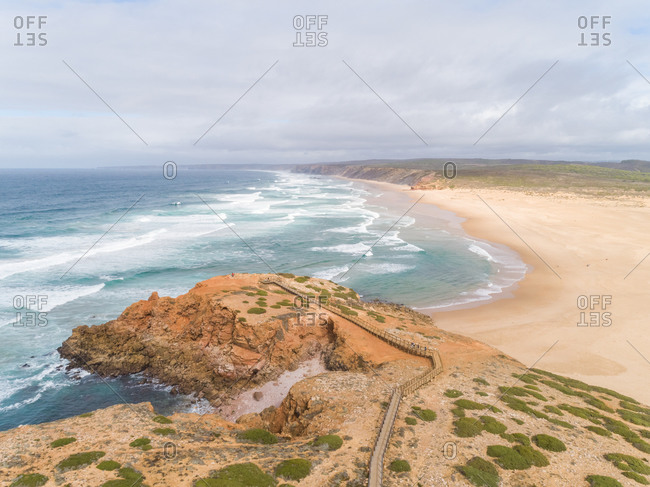 Panoramic view of the beach shore with a pier, Bordeira, Portugal