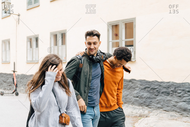 Smiling woman walking with male friends on street against building in city