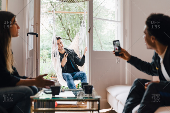 Man photographing friend with smart phone while sitting in swing at home