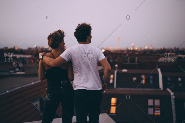 Rear view of couple with arm around looking at city while standing on terrace during dusk