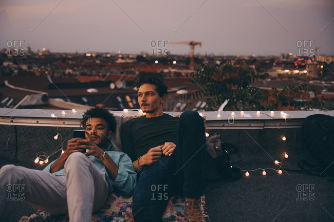 Thoughtful man sitting with friend using mobile phone on terrace in city