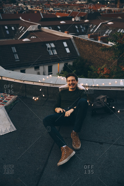 High angle full length of happy young man relaxing on illuminated terrace during party at dusk