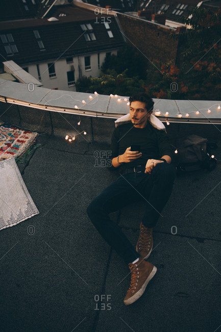 High angle full length of thoughtful man using mobile phone while relaxing on terrace during party at dusk