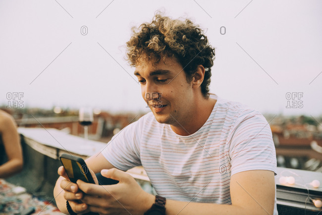 Young man text messaging through smart phone while sitting on terrace in city