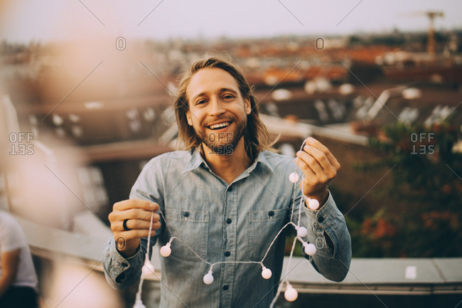Portrait of cheerful man holding string light while standing on terrace in city