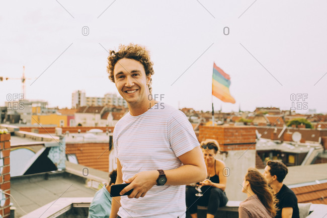 Portrait of smiling young man with mobile phone while friends enjoying on terrace during party