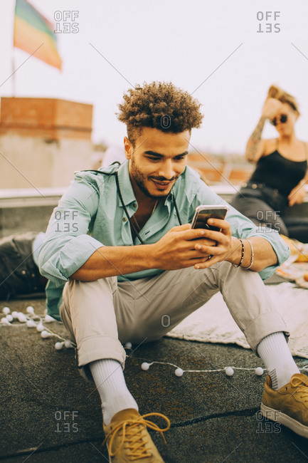 Smiling young man using smart phone while sitting on terrace at party