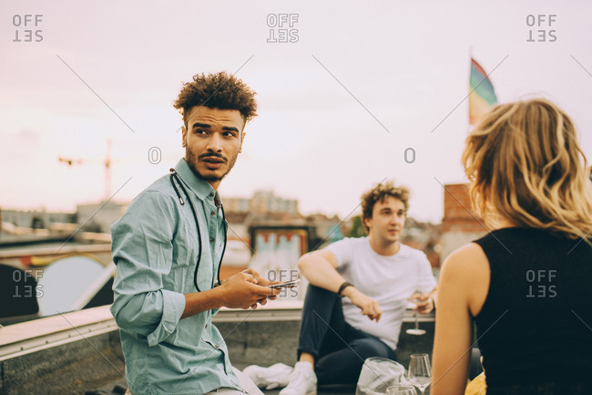Young man text messaging on smart phone while sitting with friends on terrace at rooftop party