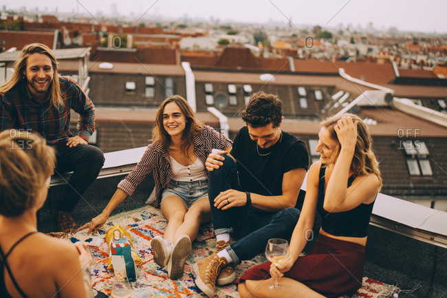 Male and female friends talking while sitting together on terrace during party