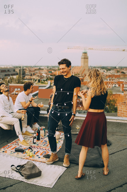 Playful woman tying string light around man while friends enjoying at rooftop party