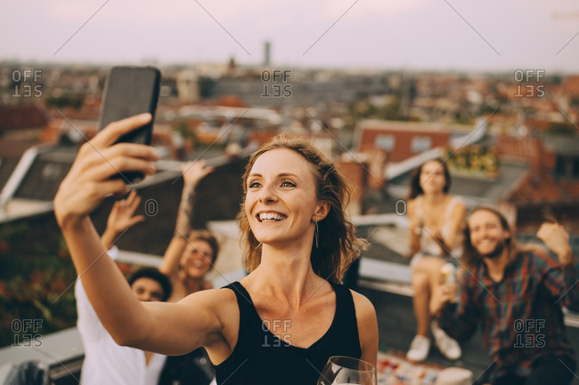 Smiling young woman taking selfie with friends through smart phone on terrace